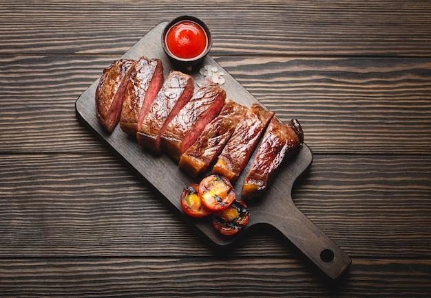 Gegrilltes oder gebratenes und in scheiben geschnittenes marmoriertes fleischsteak, tomaten als beilage und soße auf holzbrett, draufsicht, nahaufnahme, rustikaler holzhintergrund. rindersteak-lenden-konzept