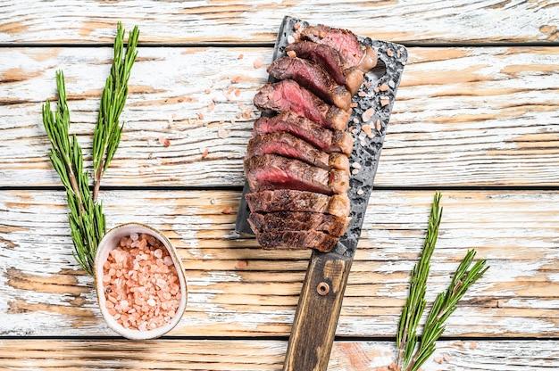 Gegrilltes ramp cap steak auf einem fleischerbeil. weiße draufsicht.