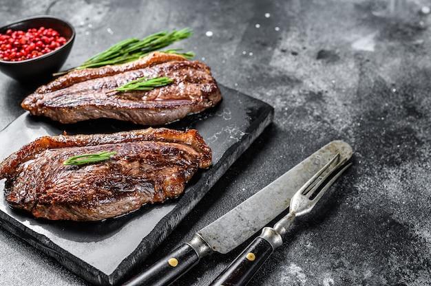 Gegrilltes ramp cap steak auf einem steinhackbrett. draufsicht. speicherplatz kopieren.