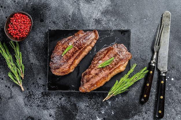 Gegrilltes ramp cap steak auf einem steinhackbrett. draufsicht.