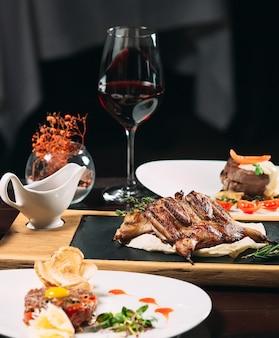 Gegrilltes rebhuhn, wolfsbarsch, tartarus. verschiedene gerichte auf dem tisch im restaurant.