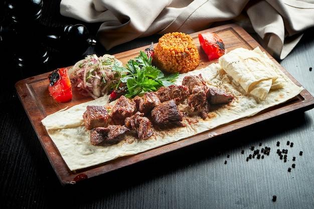 Gegrilltes rinderfilet mit bulgur und gemüse, garniert auf einem holzbrett. türkischer kebab. nahaufnahme, selektiver fokus