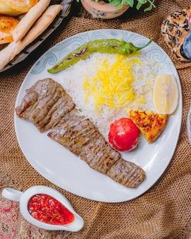 Gegrilltes rinderkotelett von oben mit reis-tomate und grünem pfeffer, gegrillt mit einer zitronenscheibe und sauce