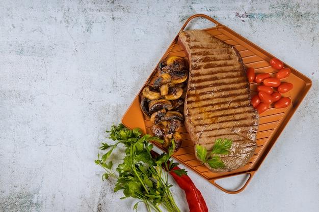 Gegrilltes rindersteak mit champignons und kräutern auf bratpfanne.