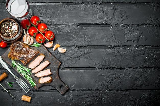 Gegrilltes rindersteak mit rosmarin und tomaten. auf einer schwarzen rustikalen oberfläche.