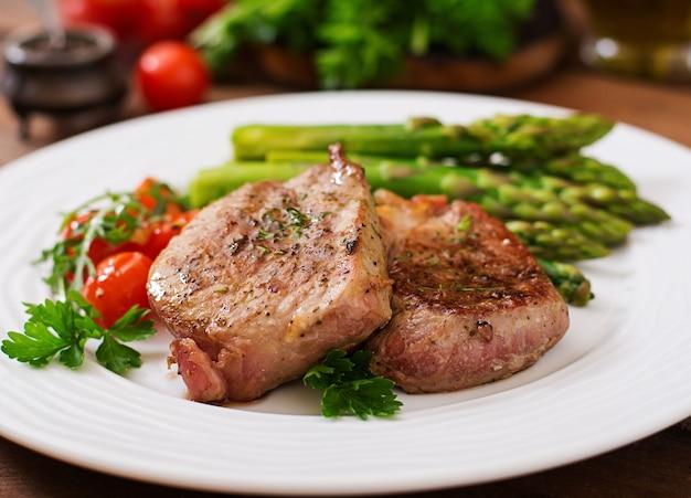 Gegrilltes rindersteakfleisch mit spargel und tomaten grillen.