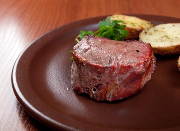 Gegrilltes rindfleisch auf weißem teller mit kartoffelsalat und tomaten. geringe schärfentiefe.