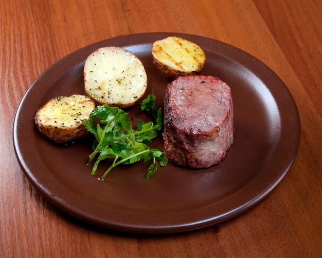 Gegrilltes rindfleisch auf weißem teller mit kartoffelsalat und tomaten