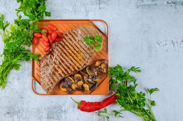 Gegrilltes rindfleisch mit champignons und tomaten.