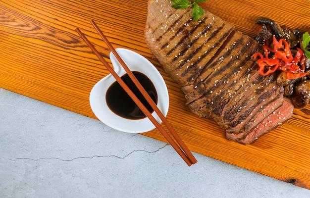 Gegrilltes rindfleisch mit sojasauce auf schneidebrett.