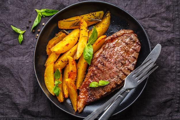 Gegrilltes rindfleischsteak mit kartoffeln und basilikum in einem schwarzblech auf dunklem hintergrund, draufsicht.