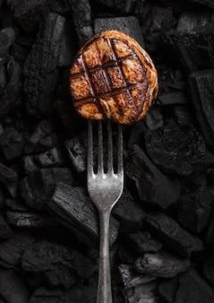 Gegrilltes saftiges rindfleischsteak auf schwarzer grillspule mit gabel