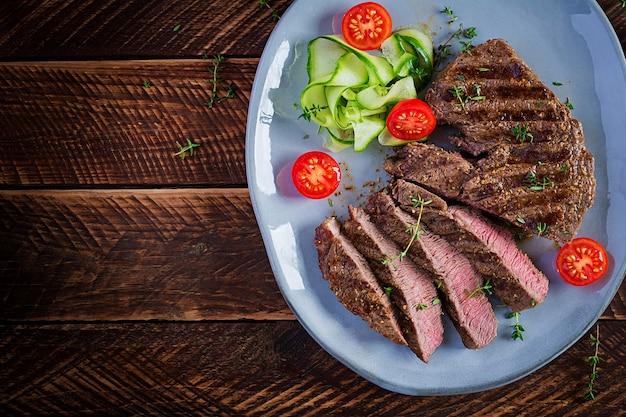 Gegrilltes saftiges steak mittleres seltenes rindfleisch mit gewürzen und frischem salat. draufsicht, oben, flach liegend