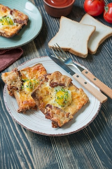 Gegrilltes sandwich mit ei, gemüse und speck auf einem dunklen hölzernen hintergrund. leckeres frühstück. platz für text.