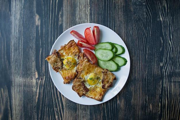 Gegrilltes sandwich mit ei, gemüse und speck auf einem dunklen holz