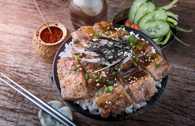 Gegrilltes scheibenschweinefleisch mit holzkohleflamme stellte auf reisschüssel in der japanischen art ein.