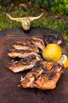 Gegrilltes schnittfleisch und geschnittene zitrone auf tabelle