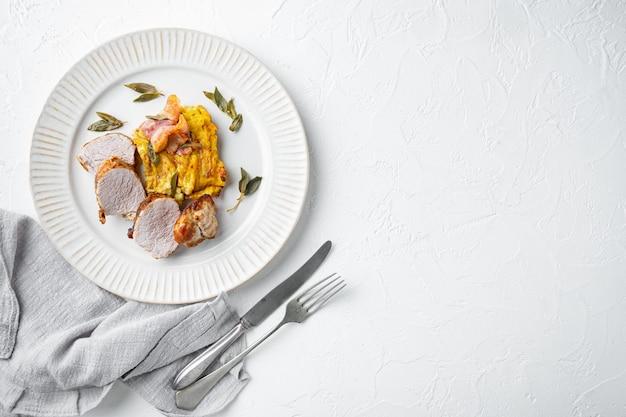 Gegrilltes schweinefilet und kartoffelpüree gratin mit salbei und prosciutto-set, auf teller, auf weißem steintisch, draufsicht flach