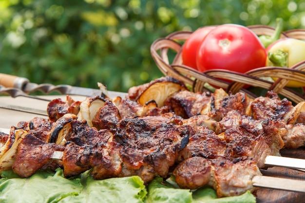 Gegrilltes schweinefleisch am metallspieß und salatblätter auf holzbrett