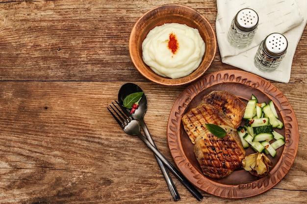 Gegrilltes schweinefleisch mit gebackenem knoblauch, frischer gurke und kartoffelpüree
