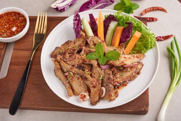 Gegrilltes schweinefleischsalat thailändisches essen mit kräutern und gewürzen zutaten, traditionelles nordöstliches essen köstlich mit frischem gemüse, scharfes und würziges stück gegrilltes schweinefleischmenü asiatisches essen. gegrilltes schweinefleisch mit würzigem dip.