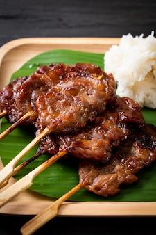 Gegrilltes schweinefleischspieß mit weißem klebreis