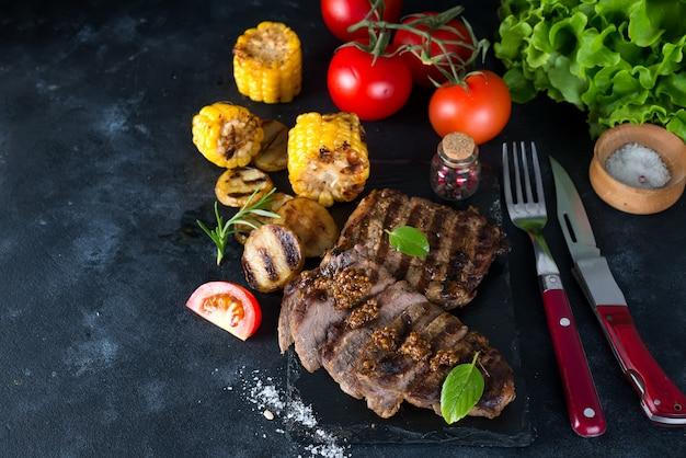 Gegrilltes schweinefleischsteak und gemüse, ofenkartoffeln und mais auf dunklem hintergrund