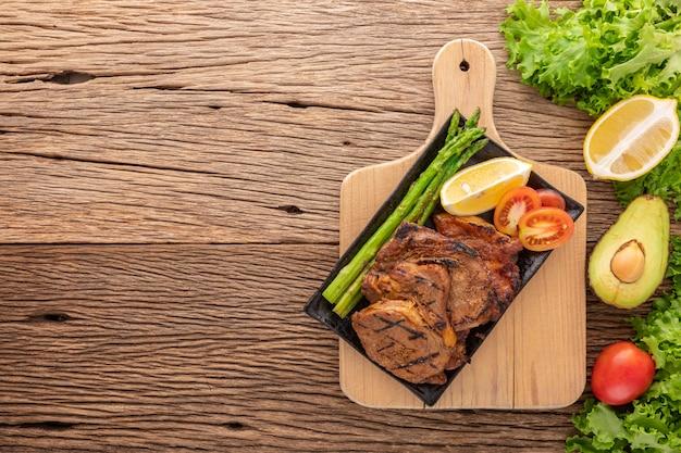 Gegrilltes schweinekotelett mit spargel in schwarzer keramikplatte neben salat, zitrone, avocado und tomate