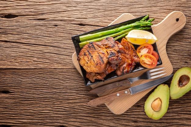 Gegrilltes schweinekotelett mit spargel, zitrone und tomate in keramikplatte auf schneidebrett neben avocado
