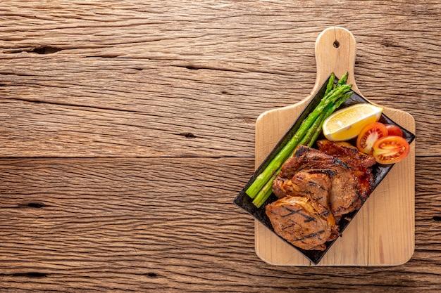 Gegrilltes schweinekotelett mit spargel, zitrone und tomate in schwarzer keramikplatte auf schneidebrett auf rustikalem naturholztexturhintergrund mit kopienraum für text, draufsicht