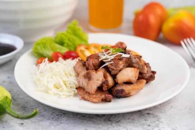 Gegrilltes schweinekotelett mit tomaten und salat, in einer weißen schüssel angeordnet.
