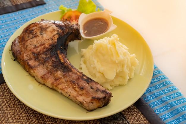 Gegrilltes schweinekotelettsteak, serviert mit kartoffelpüree und soße in einem gelben teller