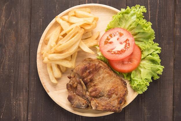 Gegrilltes schweinekotelettsteak und gemüse mit pommes frites auf holz