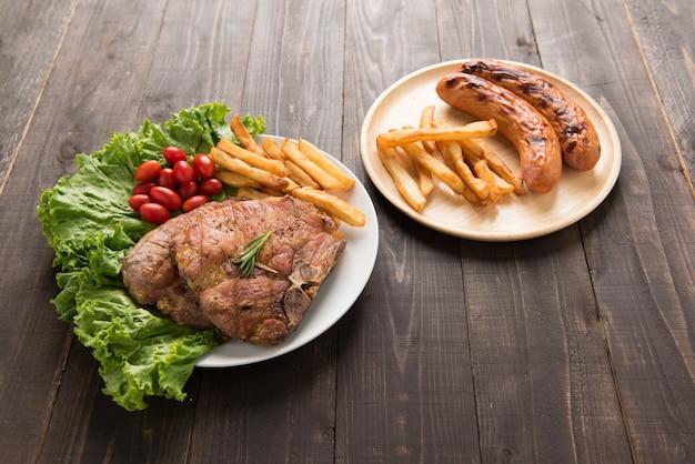 Gegrilltes schweinekotelettsteak und gemüse mit pommes frites und gegrillter wurst auf holz