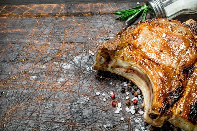 Gegrilltes schweinesteak auf knochen mit einem zweig frischem rosmarin. auf einem hölzernen hintergrund.