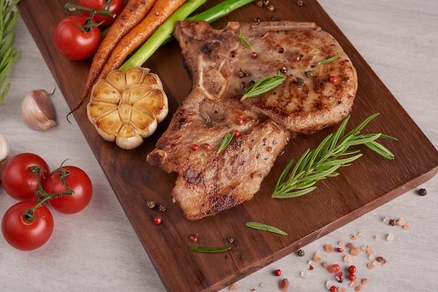 Gegrilltes schweinesteak von einem sommergrill mit gemüse, spargel, babykarotten, frischen tomaten und gewürzen. gegrilltes steak auf holzschneidebrett auf steinoberfläche. draufsicht.