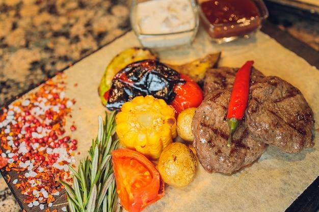 Gegrilltes seiki auf einem holzbrett mit kartoffelsauce und gemüse.