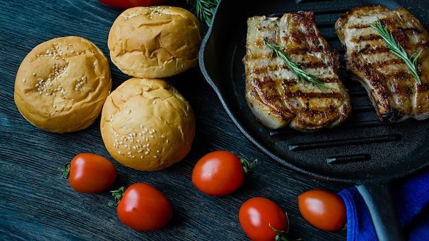 Gegrilltes steak auf einer runden grillwanne, geschmückt mit gewürzen für fleisch, rosmarin, grüns und gemüse auf einem dunklen hölzernen hintergrund.