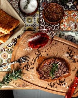 Gegrilltes steak mit einem glas wein