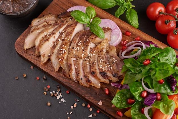 Gegrilltes steak mit frischem gemüse, paprika, tomaten, roten zwiebeln, rosa pfeffer und gewürzen. hausgemachtes leckeres essen. konzept für leckeres und gesundes essen. schwarze steinoberfläche. schweinesteak mit salat