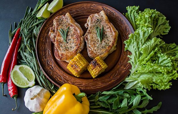 Gegrilltes steak mit gemüse in einer pfanne mit rosmarin dekoriert.