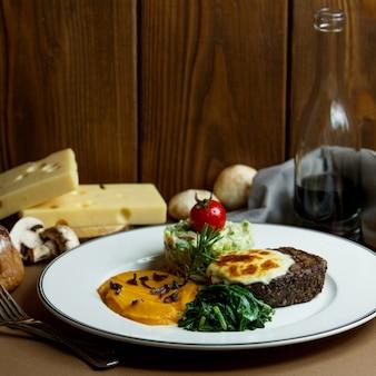 Gegrilltes steak mit geschmolzenem käse und gemüsebrei