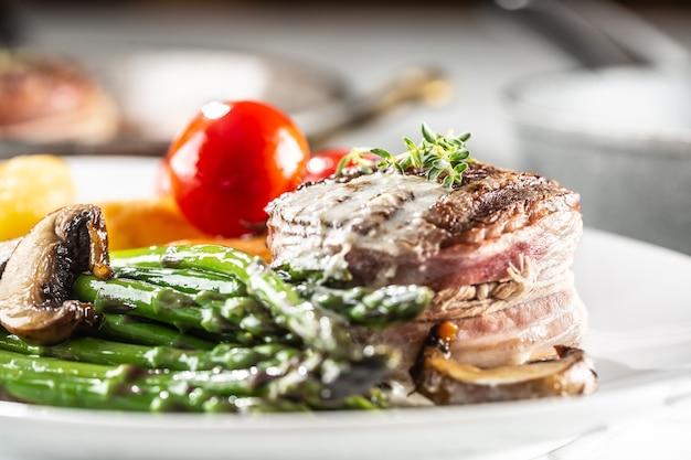Gegrilltes steak mit speck serviert auf einem teller mit spargel, champignons und tomaten.