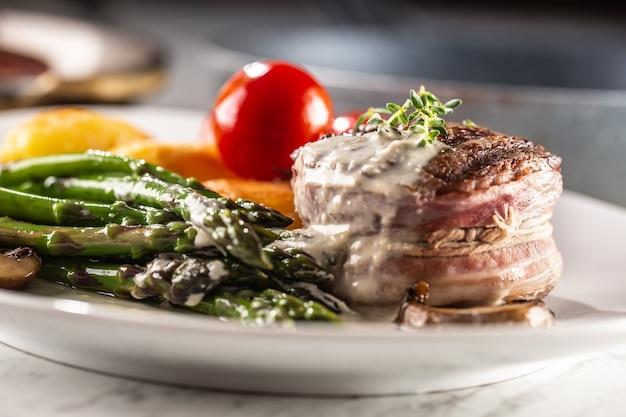 Gegrilltes steak mit speck serviert auf einem teller mit spargel und pilzsauce.