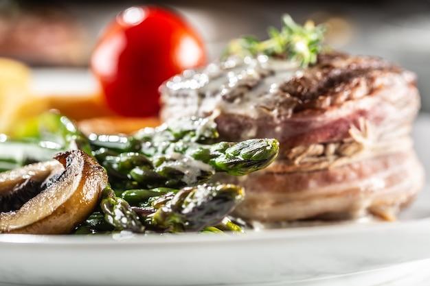 Gegrilltes steak serviert auf einem teller mit spargel, kartoffeln und tomaten.