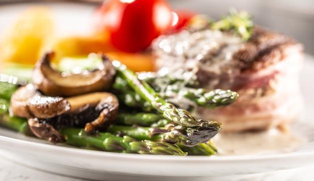 Gegrilltes steak serviert auf einem teller mit spargel, pilzen und sauce.
