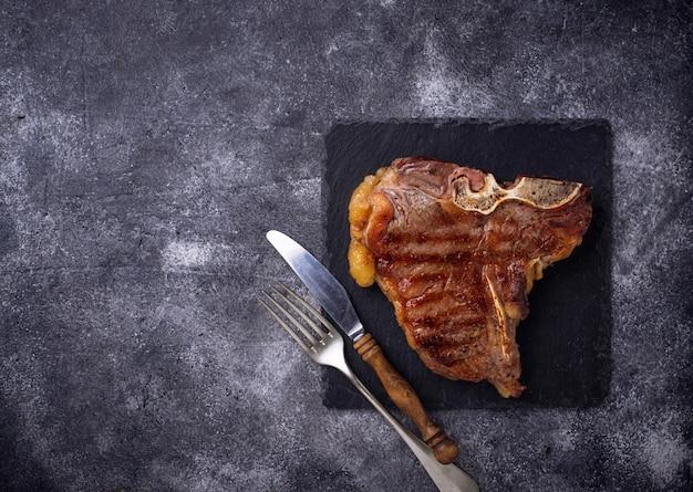 Gegrilltes t-bone-steak auf dunklem hintergrund