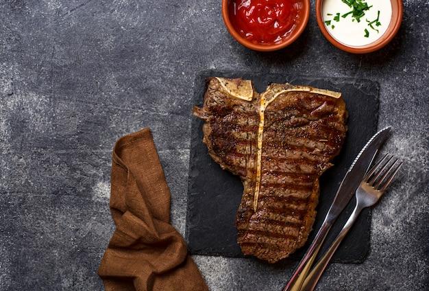 Gegrilltes t-bone-steak auf dunkler komposition