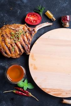 Gegrilltes t-bone-steak auf steintisch mit holzbrett. draufsicht mit textfreiraum