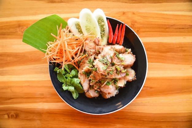 Gegrilltes thailändisches lebensmittel des schweinefleischsalats diente auf tabelle mit den kräutern und gewürzbestandteilen, die köstlich sind
